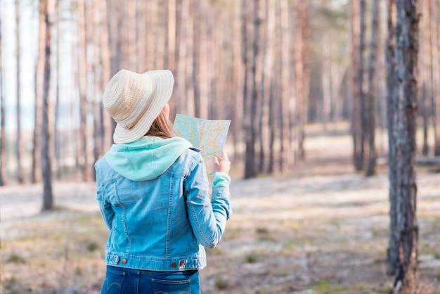 Widok z tyłu kobiety na sobie kapelusz, patrząc na mapę w lesie