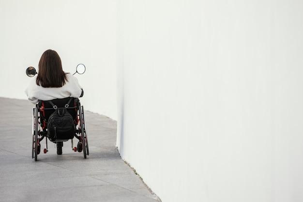 Widok z tyłu kobiety na wózku inwalidzkim z miejsca na kopię