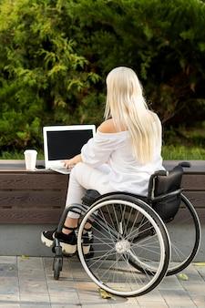 Widok z tyłu kobiety na wózku inwalidzkim za pomocą laptopa na zewnątrz