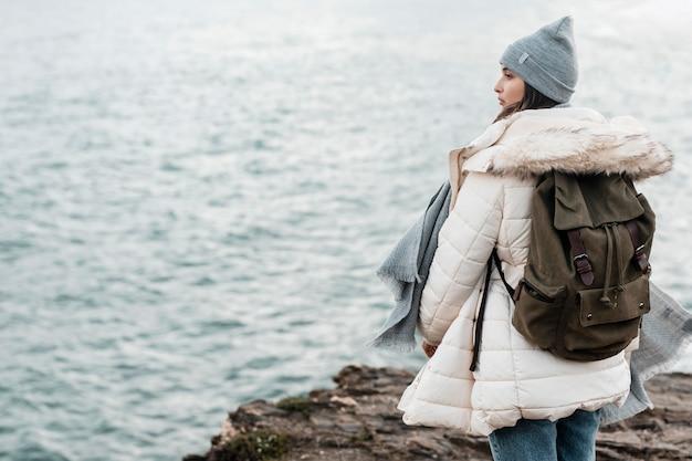 Widok z tyłu kobiety podziwiającej widok na ocean z miejsca na kopię