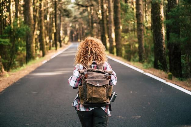 Widok z tyłu kobiety poszukiwacza przygód idącej drogą pośrodku lasu