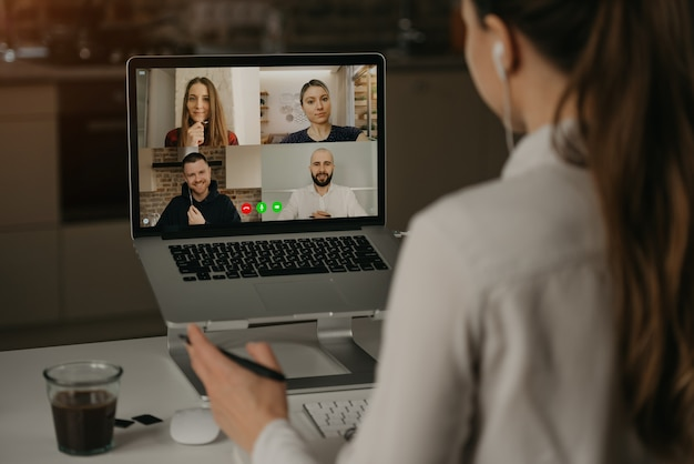 Widok z tyłu kobiety pracującej zdalnie podczas wideokonferencji z kolegami podczas spotkania online. partnerzy w rozmowie wideo.