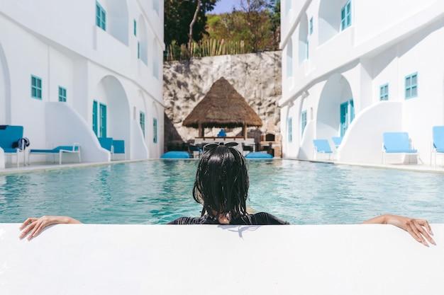 Widok z tyłu kobiety relaksującej się i odpoczywającej w basenie?