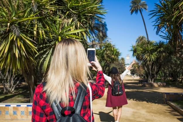 Widok z tyłu kobiety robienia zdjęć w parku