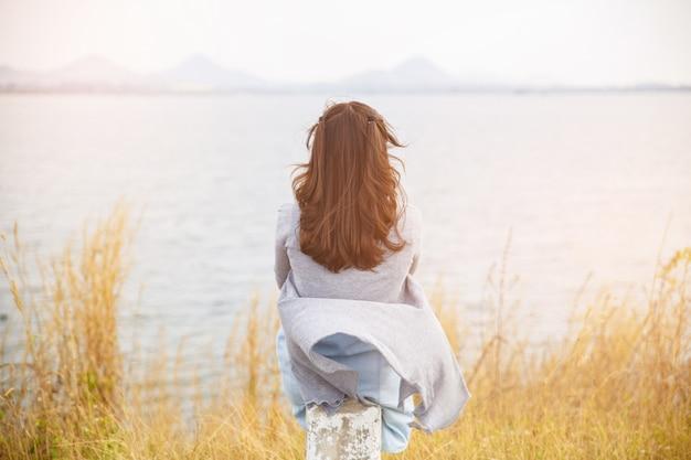 Widok z tyłu kobiety siedzą na poboczu drogi z drzewem wokół, azjatycka podróżna dziewczyna stoi odwrócić się i patrzeć daleko.