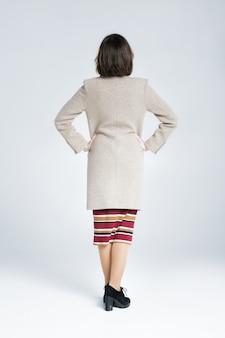 Widok z tyłu kobiety stojącej na białym tle