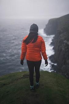 Widok z tyłu kobiety stojącej w pobliżu klifu na wyspie skye, szkocja