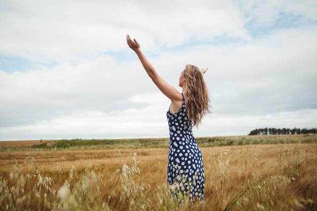 Widok z tyłu kobiety stojącej z rozpostartymi ramionami