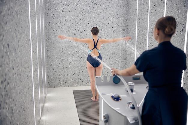 Widok z tyłu kobiety terapeutki celującej dwoma strumieniami wody w ciało pacjenta