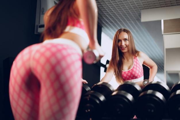 Widok z tyłu kobiety trenującej ręce z hantlami na siłowni