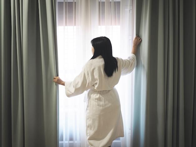 Widok z tyłu kobiety ubrana w biały szlafrok i otwierając okno zasłony w sypialni wczesnym rankiem
