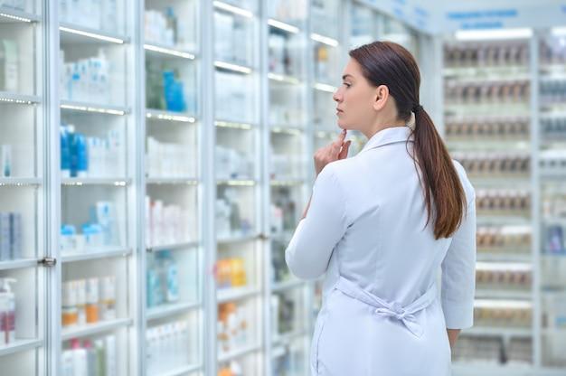 Widok z tyłu kobiety w białym fartuchu w aptece