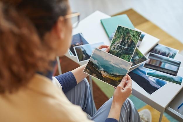 Widok z tyłu kobiety wybierającej zdjęcia do kolażu lub robiącej mapę pragnień przy stole