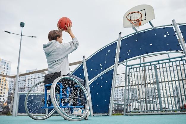 Widok z tyłu kobiety z niepełnosprawnością siedzącej na wózku inwalidzkim rzucającej piłkę do kosza na zewnątrz