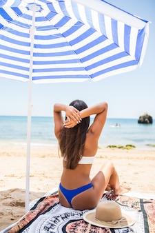 Widok z tyłu kobiety z opaloną skórą, pozowanie na plaży w słoneczny dzień. portret z tyłu stylowa dziewczyna w niebieskim bikini siedzi pod parasolami na tle morza.