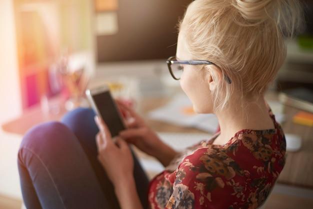 Widok z tyłu kobiety z telefonem komórkowym