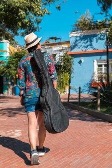 Widok z tyłu kobiety z torbą na gitarę spacerującą po parku