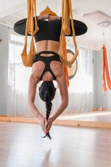 Widok z tyłu latania jogi piękna kobieta medytuje na hamakach wiszących do góry nogami pozycji lotosu