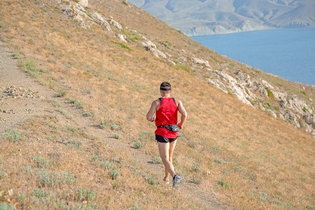 Widok z tyłu lekkoatletycznego biegacza na szlaku górskim na powierzchni błękitnego nieba