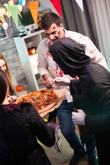 Widok z tyłu ludzi ubranych w kostiumy na halloween podekscytowany pyszną pizzą.