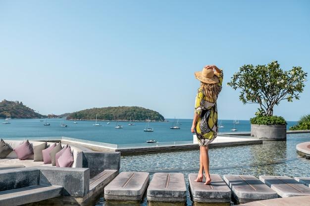 Widok z tyłu: luksusowa blondynka pozuje w pobliżu basenu bez krawędzi ze wspaniałym widokiem na morze i jachty.
