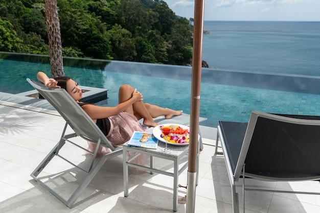 Widok z tyłu: luksusowa kobieta leży na leżaku w pobliżu basenu bez krawędzi. wakacje w krajach tropikalnych. świeże owoce
