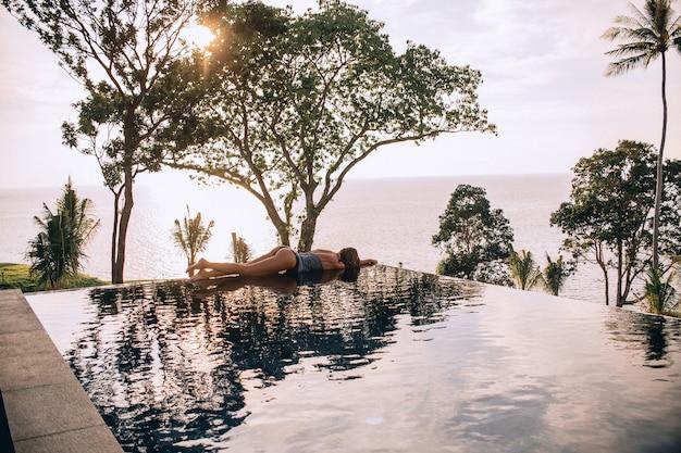Widok z tyłu luksusowe wakacje podróży kobiety relaks w basenie bez krawędzi w letnim kurorcie. kaukaski dziewczyna turysta na relaks spa wellness.