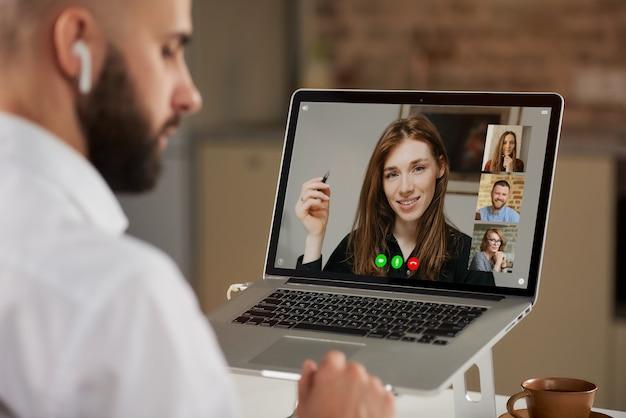 Widok z tyłu łysego pracownika płci męskiej z brodą, który słucha kolegi na wideokonferencji.