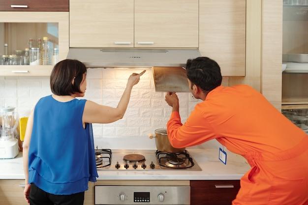 Widok z tyłu majsterkowicza rasy mieszanej w pomarańczowej odzieży roboczej usuwającej filtr przeciwtłuszczowy podczas poszukiwania problemu z okapem kuchennym, dojrzały właściciel domu wyjaśniający problem