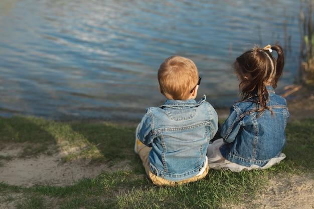 Widok z tyłu małego chłopca i dziewczynki siedzącej na brzegu stawu o zachodzie słońca