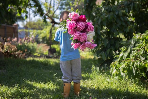 Widok z tyłu małego chłopca w dłoniach duży bukiet pięknych kwiatów piwonii