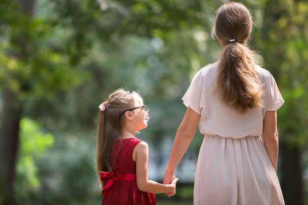 Widok z tyłu małej blond długowłosej dziewczynki z smukłą szczupłą matką w modnych sukienkach