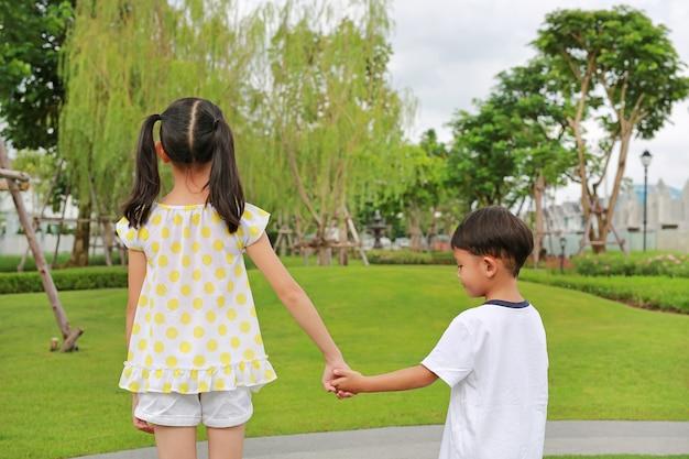 Widok z tyłu mały chłopiec i dziewczynka z ręką w ręce stoją w ogrodzie. powrót widok siostry i brata spięci w letnim parku.