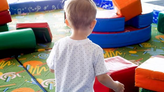 Widok z tyłu mały chłopiec maluch bawi się na placu zabaw z miękkimi przedmiotami.
