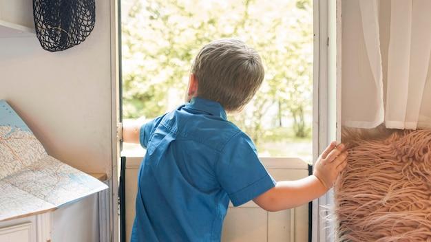 Widok z tyłu mały chłopiec otwierający drzwi przyczepy kempingowej