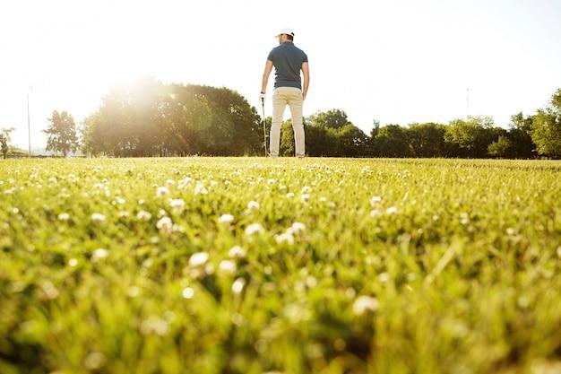 Widok z tyłu męskiego gracza w golfa na zielonym polu z klubem