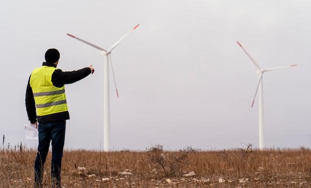 Widok z tyłu męskiego inżyniera patrząc na turbiny wiatrowe w tej dziedzinie