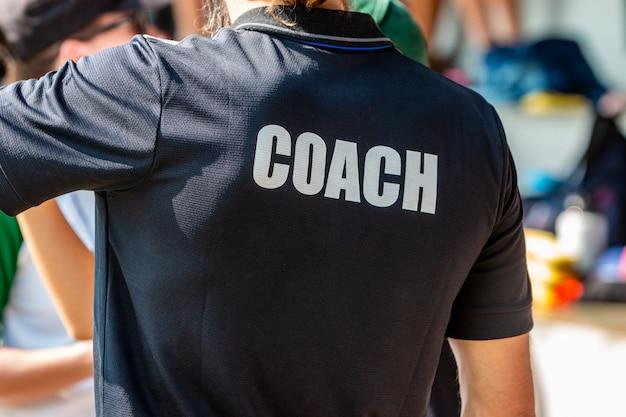 Widok z tyłu męskiego trenera w czarnej koszuli coach