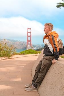 Widok z tyłu męskiego turysty patrzącego na most golden gate w san francisco