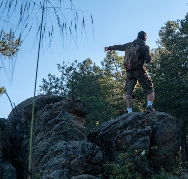 Widok z tyłu męskiego turysty wskazującego lewą pozycję na skale. mężczyzna z plecakiem wskazujący na bok stojący na skale w górskiej scenie.