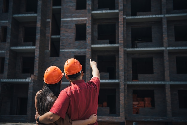 Widok z tyłu: mężczyzna i kobieta w pomarańczowych hełmach stoją, obejmując się ramionami i patrzą na murowany apartamentowiec w budowie.