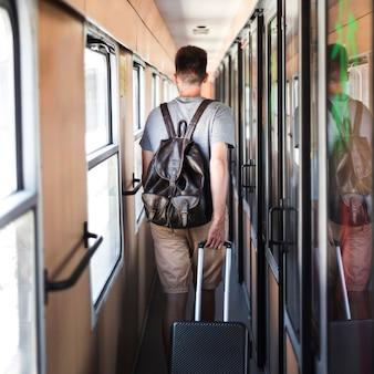 Widok z tyłu mężczyzna idący w pociągu