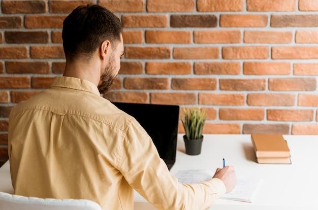Widok z tyłu mężczyzna o rozmowie wideo na laptopie