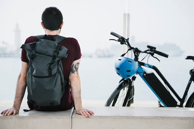 Widok z tyłu mężczyzna siedzący obok swojego e-roweru