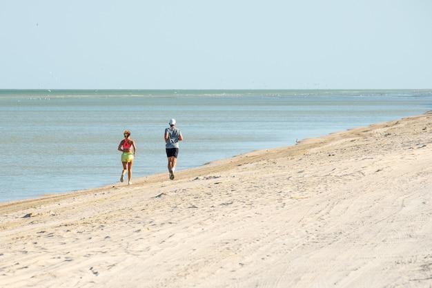 Widok z tyłu mężczyzny i kobiety biegnących wzdłuż plaży wzdłuż morza