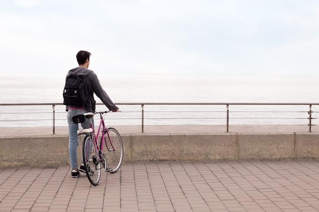 Widok z tyłu mężczyzny idącego rowerem z koncepcją zrównoważonego transportu i miejskiego stylu życia