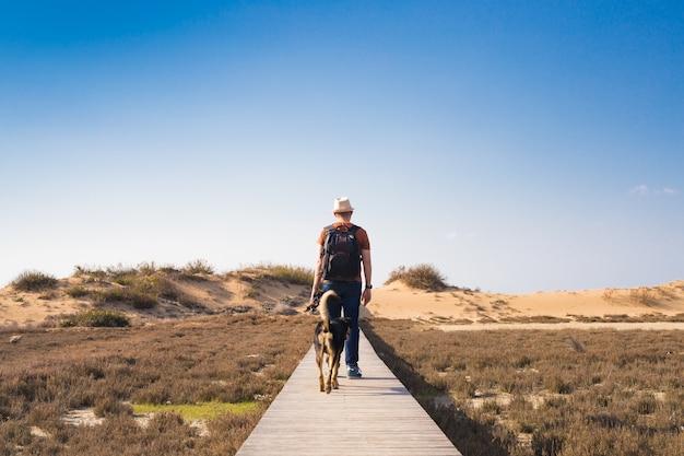 Widok z tyłu mężczyzny idącego z psem drogą prowadzącą przez piękny krajobraz.