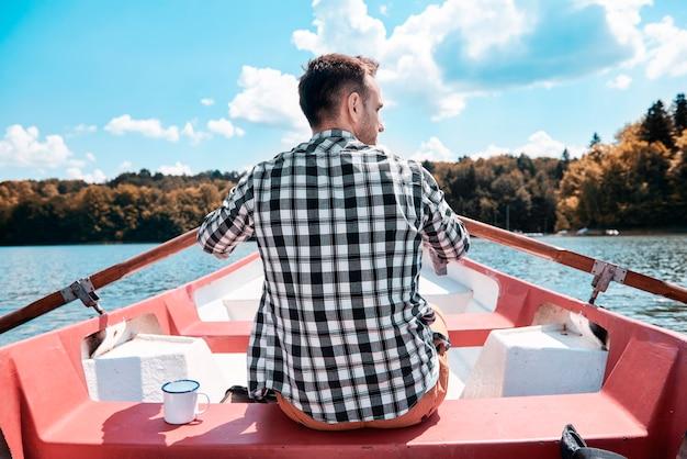 Widok z tyłu mężczyzny pływającego kajakiem i podziwiającego widok