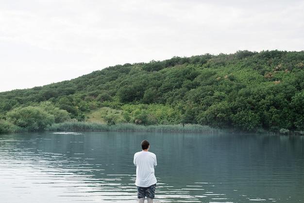 Widok Z Tyłu Mężczyzny Stojącego W Pobliżu Jeziora Premium Zdjęcia