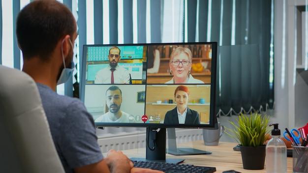 Widok z tyłu mężczyzny z maską rozmawiającego na rozmowie wideo z kolegami zdalnie. freelancer pracujący w nowym, normalnym biurze, rozmawiający podczas wirtualnej konferencji, spotkania, korzystający z technologii internetowej